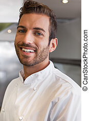 Cheerful handsome young chef looking at camera