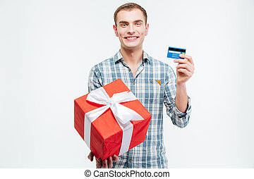 Cheerful handsome young man holding present and credit card