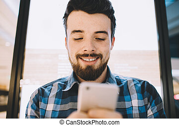Cheerful handsome young man using his smartphone for chatting with friends