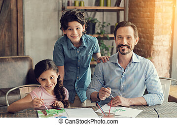 Cheerful happy family looking at you