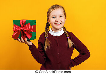 Cheerful happy little girl is holding a box with a gift. A child in a burgundy sweater on a yellow background
