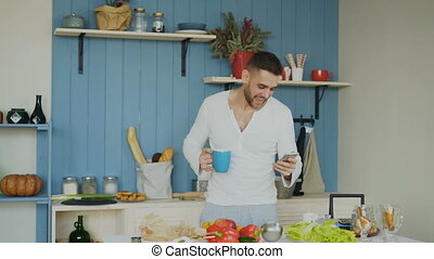 Cheerful happy man dancing and singing in kitchen while...