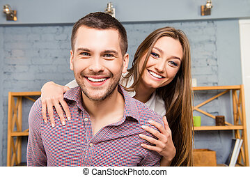 Cheerful happy man piggybacking his pretty girlfriend