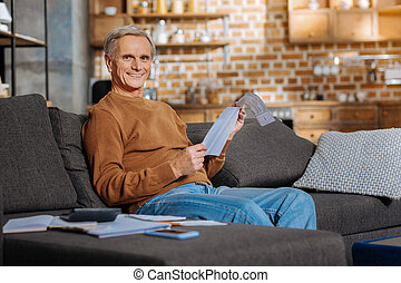 Cheerful happy man reading a document