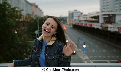 cheerful, happy, smiling girl standing on the bridge, have fun, posing looks at the camera. slow motion