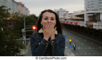 cheerful, happy, smiling girl standing on the bridge, sends kisses, have fun, looks at the camera.