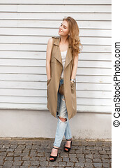 Cheerful happy young woman in a summer vest in a stylish T-shirt in stylish ripped jeans in black high heel shoes with a black handbag posing near a wooden white vintage wall. Cute girl on a walk