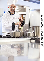 Cheerful head chef flavoring food with pepper in professional kitchen