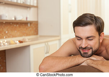 Cheerful healthy man is attending beauty salon