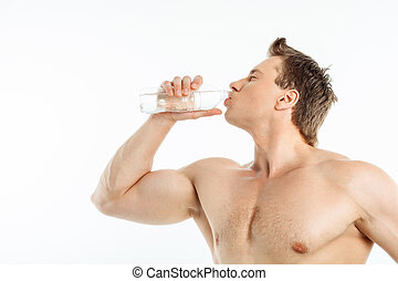 Cheerful healthy young man is very thirsty