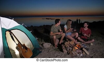 Cheerful hiking friends relaxing near campfire, surfing the...
