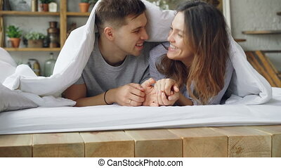 Cheerful husband is talking to his attractive wife and kissing her while lying in bed together, happy couple is smiling and laughing. Romantic relationship concept.