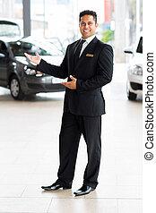 indian car salesman doing welcoming gesture