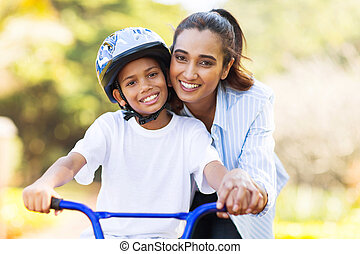indian mother teaching her son to ride a bike