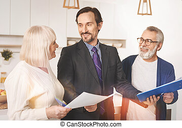 Cheerful insurance agent working with retired couple