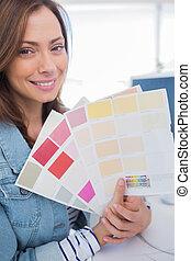 Cheerful interior designer holding up colour samples close...