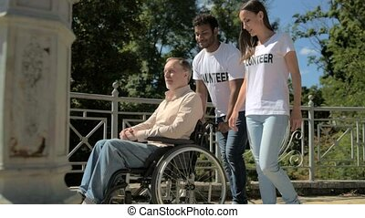 Cheerful international volunteers walking with a wheelchaired man