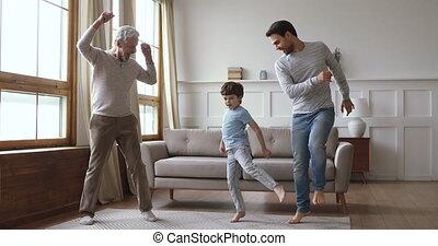 Cheerful joyful multi generation men family dancing at home