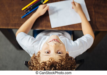 Cheerful kid drawing and smiling into camera
