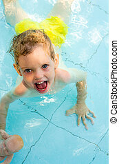 Cheerful kid in the swimming pool water