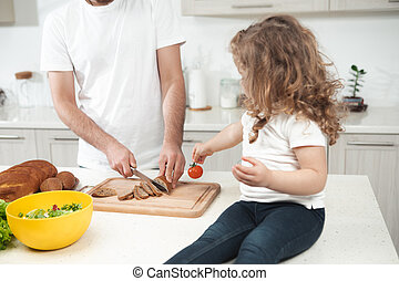 Cheerful kid spending time with dad in cook room