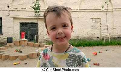 Happy little boy with toothy smile looking at camera while standing on sandy playground in yard of house in summer day
