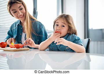 Cheerful kid tasting healthy food in kitchen