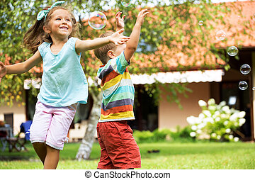 Cheerful kids chasing the soap bubbles