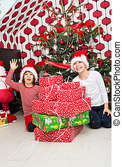 Cheerful kids with many Christmas gifts
