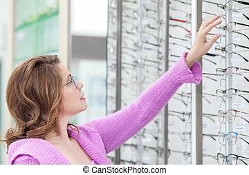 Cheerful lady is choosing eyeglasses in shop