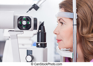 Cheerful lady is getting ophthalmology diopters calibration...