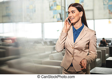 Cheerful lady speaking on smartphone in hall