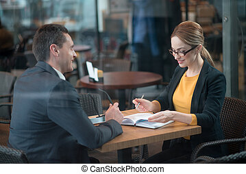 Cheerful lady speaking with colleague in cafe