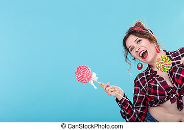 Cheerful laughing pretty young woman in retro clothes posing on a blue background with a lollipops showing the right side. Concept of link and information on the right. Copyspace.