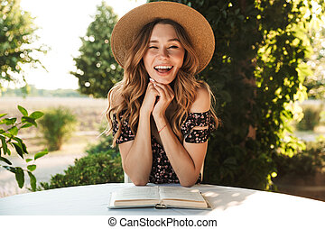 Cheerful laughing young woman sitting in cafe outdors in park with book.