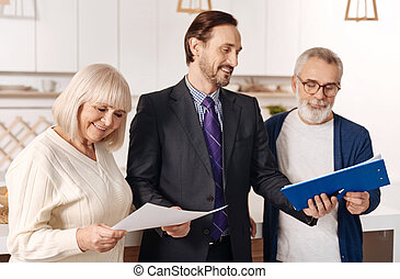 Cheerful lawyer demonstrating contract for elderly couple of clients
