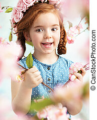 Cheerful litlle girl holding a branch