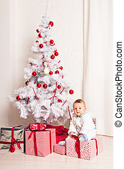 Cheerful little baby boy playing near Christmas tree