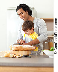 Cheerful little boy and his father cutting bread