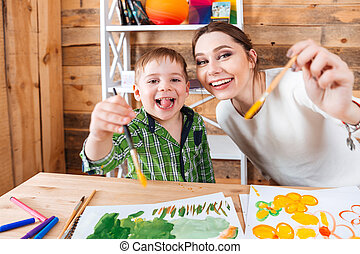 Cheerful little boy and his mother showing paintbrushes to...