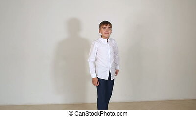 Cheerful little boy in black pants and white shirt jumping on white background.