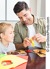 Cheerful little boy making paper shapes with father at the...