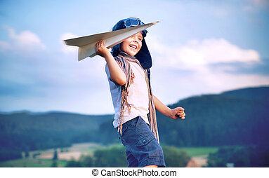 Cheerful little boy playing paper plane