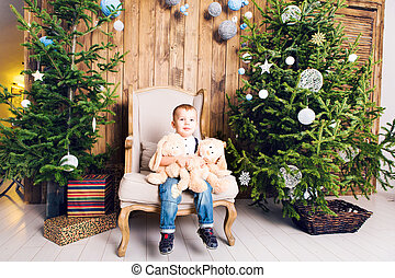 Cheerful little boy playing with his toy by the Christmas tree
