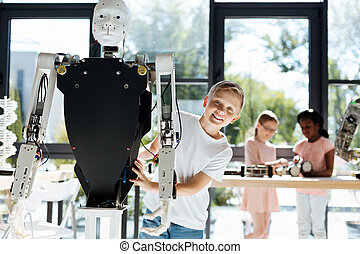 Cheerful little boy posing with a human robot