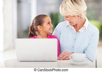 little girl and grandma using laptop