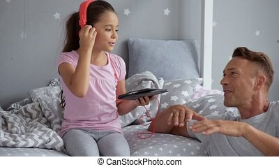 Cheerful little girl and her father singing song