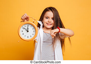 Cheerful little girl child pointing to clock alarm.