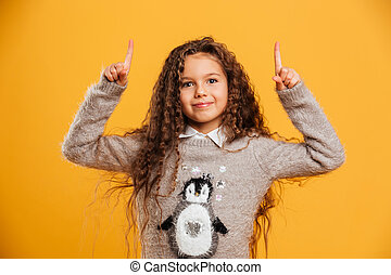 Cheerful little girl child standing isolated pointing.