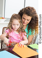 Cheerful little girl cutting paper with mother at the table